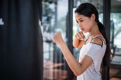 Beautiful woman practicing boxing in gym. she punch to punching bag. royalty free stock photo