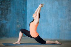 Beautiful woman practicing low lunge exercise. Side view of beautiful young woman dressed in bright sportswear enjoying yoga indoors. Yogi girl working out in royalty free stock image
