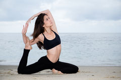 Beautiful woman practicing yoga at beach Stock Photos