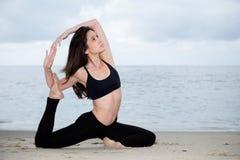 Beautiful woman practicing yoga at beach Stock Photos