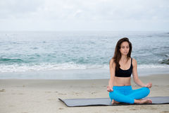 Beautiful woman practicing yoga at beach Stock Images