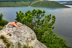 Beautiful woman is practicing yoga on green mat on rock against river. Stock Photo