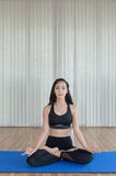 Beautiful woman practicing yoga and gymnastic on blue mat Royalty Free Stock Photos