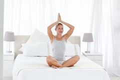 Beautiful woman practicing yoga on her bed Stock Images