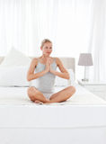Beautiful woman practicing yoga on her bed Stock Image