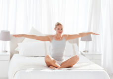 Beautiful woman practicing yoga on her bed Stock Photos