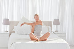 Beautiful woman practicing yoga on her bed Stock Photo