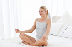 Beautiful woman practicing yoga on her bed Royalty Free Stock Photography