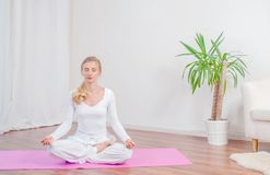 Beautiful woman is practicing yoga at home on yoga mat, girl sitting in Lotus pose stock photo