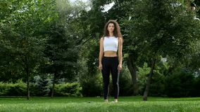 Beautiful woman practicing yoga in the park stock footage