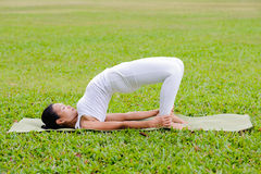 Beautiful woman practicing yoga in the park Stock Photography