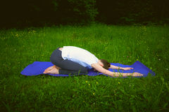 Beautiful woman practicing yoga in the park Child's Pose Balasana. Royalty Free Stock Photos