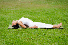 Beautiful woman practicing yoga in the park stock photo
