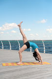 Beautiful woman practicing yoga on the sea Royalty Free Stock Photos