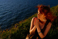 Beautiful woman praying by sea Stock Photography