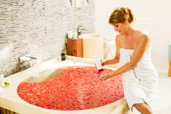 Woman preparing romantic bath with flowers and using bathing product. Beautiful woman preparing romantic bath with flowers and using bathing product Stock Images