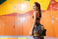 Beautiful woman preparing to climb up the wall stock photo