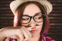Beautiful woman pretending to have a fake moustache. Against brick wall Stock Photography