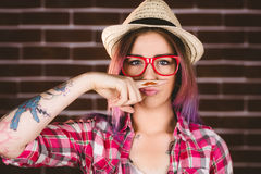 Beautiful woman pretending to have a fake moustache. Against brick wall Stock Image