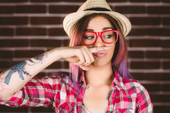 Beautiful woman pretending to have a fake moustache. Against brick wall Royalty Free Stock Image