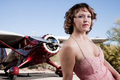 Beautiful woman with private plane. A beautiful young woman waits by a private plane Royalty Free Stock Images
