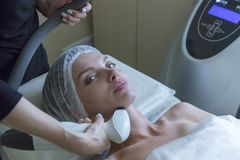Beautiful woman in professional beauty salon during radio lifting procedure royalty free stock photography