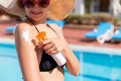 Beautiful woman protecting her skin against sunburn, applying sun lotion on her shoulder by the pool. Sun Protection Factor in. Vacation, concept stock photos