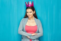 Beautiful woman is proud her big breast. Portrait of girl with paper crown, blue wall back Stock Photography