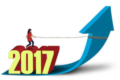 Beautiful woman pulling arrow with number 2017 royalty free illustration