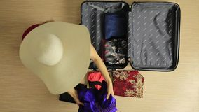 Beautiful woman pulls out dresses in suitcase for the trip stock video footage
