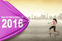 Beautiful woman pulls text of healthy resolution for 2016 Royalty Free Stock Image
