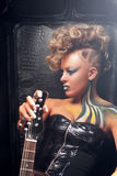 Beautiful woman punk with bass guitar profile. Attractive rocker girl in leather cloth, with bright body art and hairstyle, posing with her musical instrument royalty free stock photos