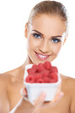 Beautiful woman with punnet of raspberries. Beautiful smiling blonde woman with punnet of fresh ripe raspberries with focus to her blue eyes Stock Photography