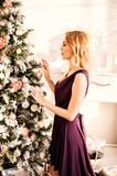 Beautiful woman in purple dress decorate the Christmas tree Royalty Free Stock Image