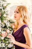 Beautiful woman in purple dress decorate the Christmas tree Stock Images