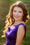 Beautiful woman in a purple dress on the meadow Royalty Free Stock Photography