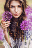Beautiful woman among purple flowers Stock Photography