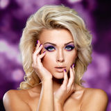 Beautiful woman with purple makeup of eyes. Beautiful blond woman with purple makeup of eyes. Fashion model with curly hairstyle. Blinking Background. Bokeh royalty free stock image