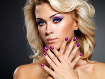 Beautiful woman with purple manicure and makeup. Beautiful blond woman with beauty purple manicure and makeup of eyes. Fashion model with curly hairstyle royalty free stock image