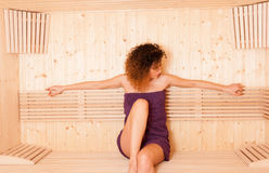 Beautiful woman in purple towel relaxing in sauna room Royalty Free Stock Image