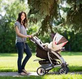 Beautiful Woman Pushing Baby Carriage In Park. Portrait of beautiful young woman pushing baby carriage in the park royalty free stock image