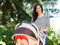 Beautiful Woman Pushing Stroller In Park. Portrait of beautiful young woman pushing stroller in park stock photography