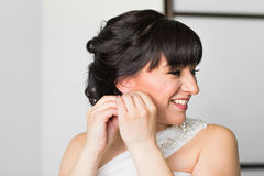 Beautiful woman put earring and smiling portrait Royalty Free Stock Photography