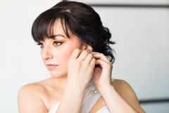 Beautiful woman put earring Royalty Free Stock Photo