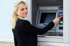 Beautiful woman put her credit card at the ATM Stock Images