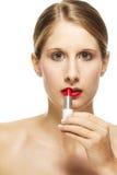 Beautiful woman put on lipstick Stock Photography