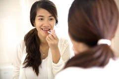 Beautiful woman put make up on, applying lipstick on her lips Stock Photos