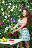 Beautiful woman puts bunch of flowers on table Stock Image
