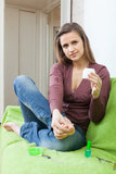 Beautiful woman puts cream on foot Stock Photo