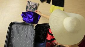 Beautiful woman puts dresses in suitcase for the trip stock video footage